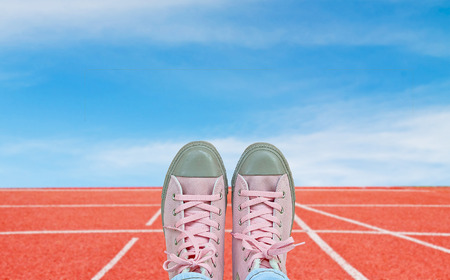 arduous: pink and brown sneakers with running track number standard red color under the blue sky, concept of start.