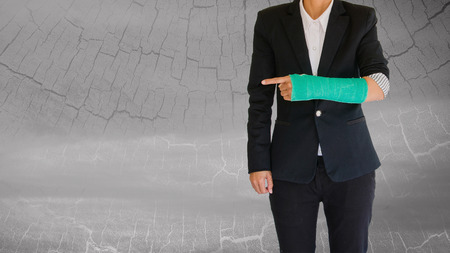 cast: Injured businesswoman with green cast on hand and arm on blurred abstract background. Stock Photo