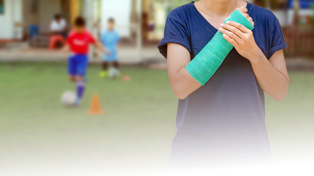 broken arm with green cast on blurred background kid soccer player in academy - insurance concept Stock Photo