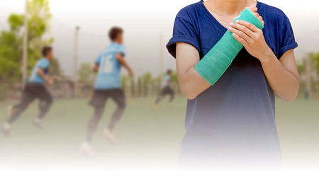 broken arm: broken arm with green cast on blurred background kid soccer player in academy - insurance concept Stock Photo