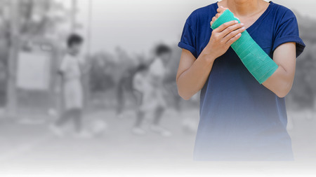 cast: broken arm with green cast on blurred background kid soccer player in academy - insurance concept Stock Photo