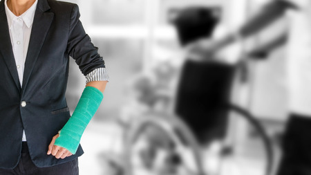 arm broken with green cast on blurred patient sitting in wheelchair background - insurance concept