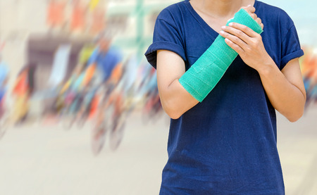 broken wrist: arm broken with green cast on blurred cyclists riding in city  - insurance concept Stock Photo