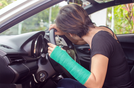 sick person: woman with broken hand in cast sitting in car, insurance concept
