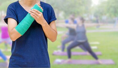 fisioterapia: brazo roto con el elenco verde en grupo fitness mujer borrosa - equipo de yoga Foto de archivo
