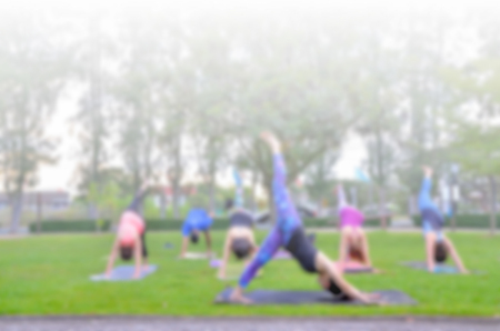 outdoor training: blurred woman fitness group - yoga team