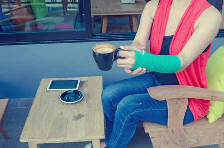 cast: injured woman with green cast on the wrist holding black coffee cup and smart phones on wood table  in coffee cafe. Stock Photo