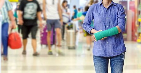 injured woman with green cast on hand and arm on traveler in motion blur in airport interior background, Travel insurance concept.
