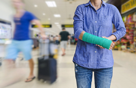 Injured woman with green cast on hand and arm on traveler in motion blur in airport interior background, Travel insurance concept. Standard-Bild