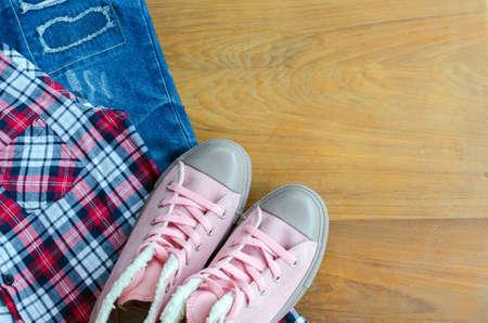 scott: Pink sneaker, scott shirt, torn jean on wood table, Travel accessories.