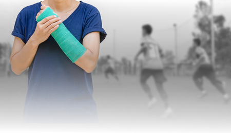 broken arm with green cast on blurred background kid soccer player in academy. Standard-Bild