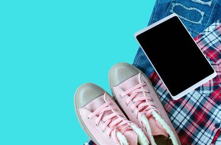 scott: Pink sneaker, scott shirt, torn jean, smart-phone isolated on blue background.