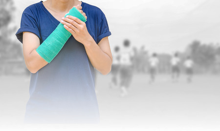 broken arm with green cast on blurred background kid soccer player in academy. Stock Photo