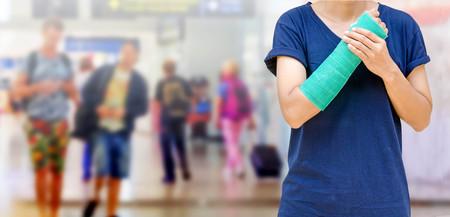 luxacion: Accidente en el brazo, Mujer lesionada con el elenco verde en la mano y el brazo en el viajero en desenfoque de movimiento en el aeropuerto de fondo interior,, concepto de lesión corporal.