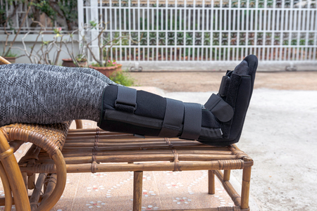 injury woman with black splint on leg  sitting on wooden chair at home, Travel insurance concept.