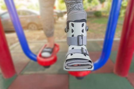 splint: Mujer lesionada llevaba ropa deportiva roto tobillo llevaba soporte de tobillo en equipo de ejercicio en un fondo de parque público, concepto de seguro.