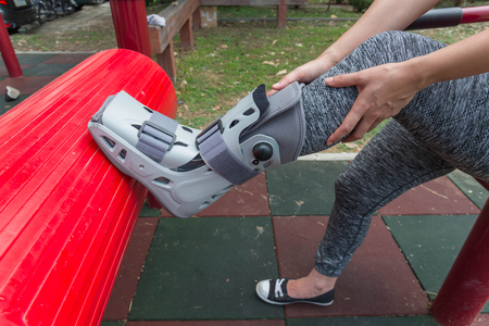 injured woman wearing sportswear  broken ankle wearing ankle support on exercise equipment in a public park background, insurance concept.