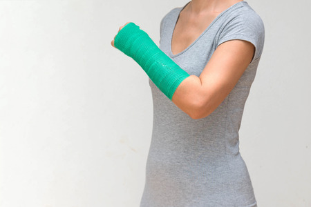 Injury woman wearing sports ware with green cast on hand and arm, body injury concept. Stock Photo
