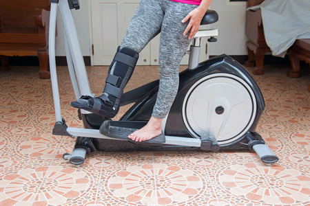 injury woman with black splint on leg  standing on exercise bike at home, insurance concept