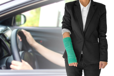 insurance concept, injured businesswoman with green cast on hand and arm  and wearing black suit standing isolated on blurred background woman hand driving car. Imagens