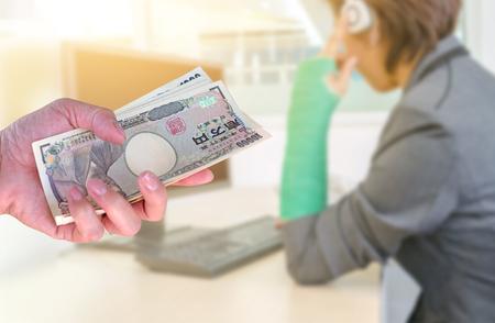 splint: Costo de la atención médica, mujer de la mano con moneda japonesa yenes billetes de banco en fondo borroso mujer de lesión con ropa deportiva con férula negra en la pierna sentado en el piso