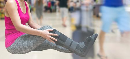 splint: broken leg, injury woman wearing sportswear and ankle support, leg cast, leg splint on traveler in motion blur in airport interior.