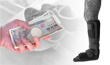 splint: Concepto de seguro, mujer de mano de primer plano con billetes de banco de yenes de moneda japonesa sobre mujer de lesiones con tablilla negra en la pierna de pie sobre fondo borroso zapatos viejos en patineta. Foto de archivo