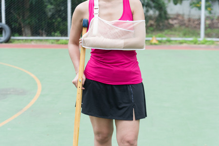 Injured woman wearing sportswear  painful arm with gauze bandage, arm sling and wooden crutches on basketball court. Stock Photo