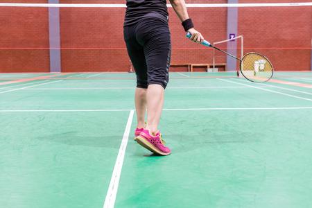 バドミントンコートでラケットとシャッターコックを持って立っているスポーツウェアを着たバドミントン女子選手 写真素材