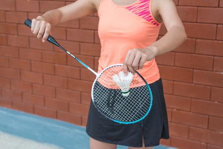 バドミントン ラケットとシャッター コックを保持しているスポーツウェア立ってを身に着けて女性プレイヤー。
