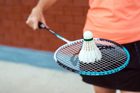ラケットとシャッターコックを持って立っているスポーツウェアを着たバドミントン女子選手。 写真素材