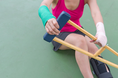Injury woman wearing sportswear  painful arm  and leg with gauze bandage, arm cast and wooden crutches sitting on green floor.