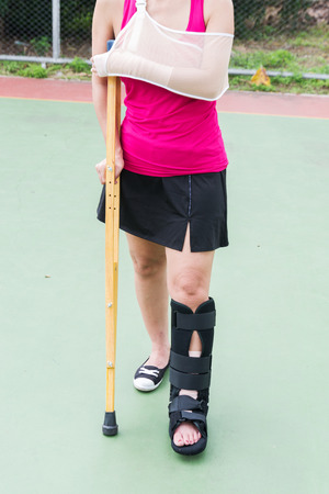 splint: Injured woman wearing sportswear painful arm and leg with gauze bandage, arm sling and painful leg with black cast and wooden crutches on green floor. Foto de archivo