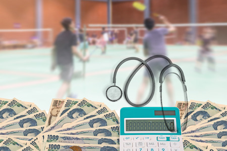 Health care cost, Top view stethoscope with calculator, Japanese currency yen bank notes and Japanese coin on blurred background badminton player in court. Stock Photo