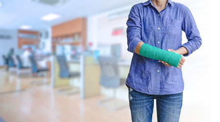 worker woman accident on arm with green arm cast on blurred business office working space background Standard-Bild