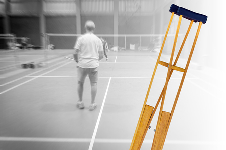 crutches for patient broken leg isolated on blurred background badminton old man player, injury from sport concept.