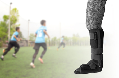 injured leg with black splint on leg standing on blurred background soccer player running.