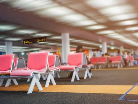 row of seats in departure area in airport terminal.