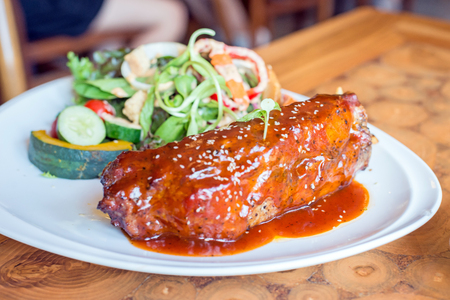barbecue pork ribs steak served with french fries and vegetables on a white plate.