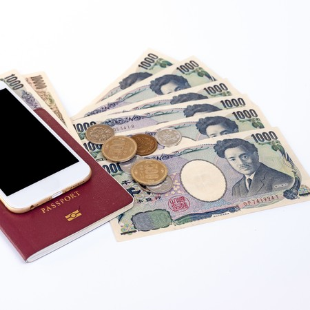 Japanese currency yen bank notes with Japanese yen coin, phone and passport on white background. Stock Photo