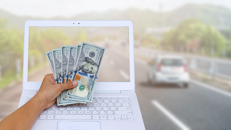 Business woman hand holding American dollar currency on white laptop isolated on blurred cars run on a Japanese highway with mountain background, clipping path include.