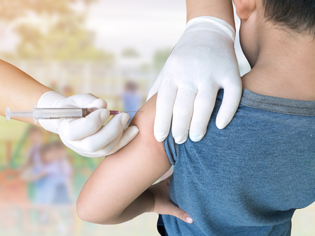 Doctor woman giving a child injection in arm on burred student playing with toy on playground in the school.