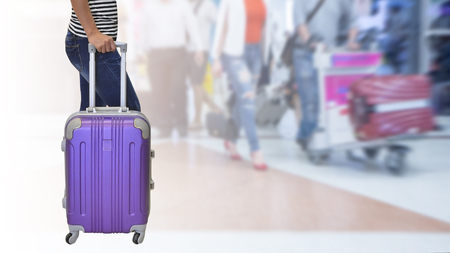 Female passenger was wearing jeans and a black and white shirt standing and holding her hand a purple suitcase with background airport , travel concept. Stock fotó