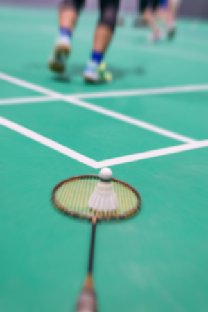 blurred badminton shuttlecock and racket on court.