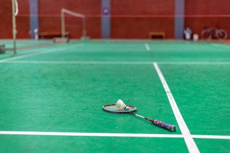 badminton shuttlecock and racket on green court. Stock Photo