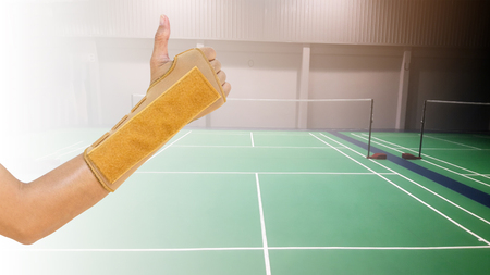 hand with wrist support on background badminton indoor court, sport accident pain concept. Stock Photo