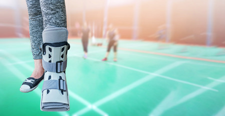 Broken leg with short splint for treatment of injured woman standing and wearing sportwear isolated on blurred background badminton player and green court. Banco de Imagens