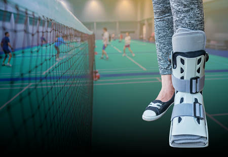 Broken leg with short splint for treatment of injured woman standing and wearing sportwear isolated on badminton net in the badminton court. Banco de Imagens