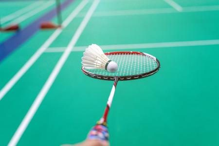hand holding badminton shuttlecock with racket on court. Standard-Bild - 112670089