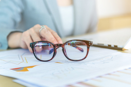 Closeup eyeglasses and female hand on background laptop and graph report data on wood desk working at the office. Standard-Bild - 112670094